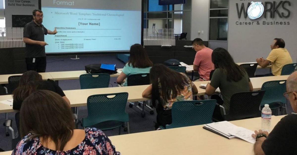 John Savercool enseña a una clase de estudiantes que se enfrentan a una pantalla sobre formatear en San Jose Public Library Trabajos de aula.