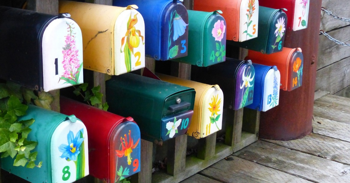 Mailboxes with flowers and apartment numbers painted on them.