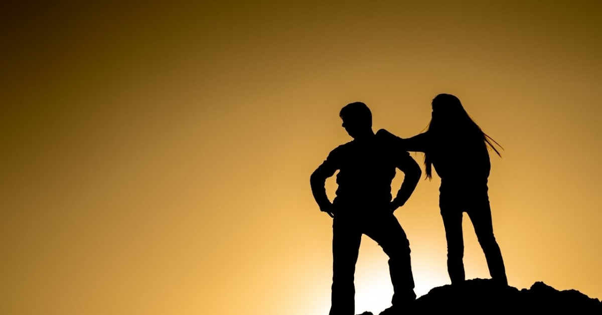 Sillouettes of man and woman on top of a mountain at sunset