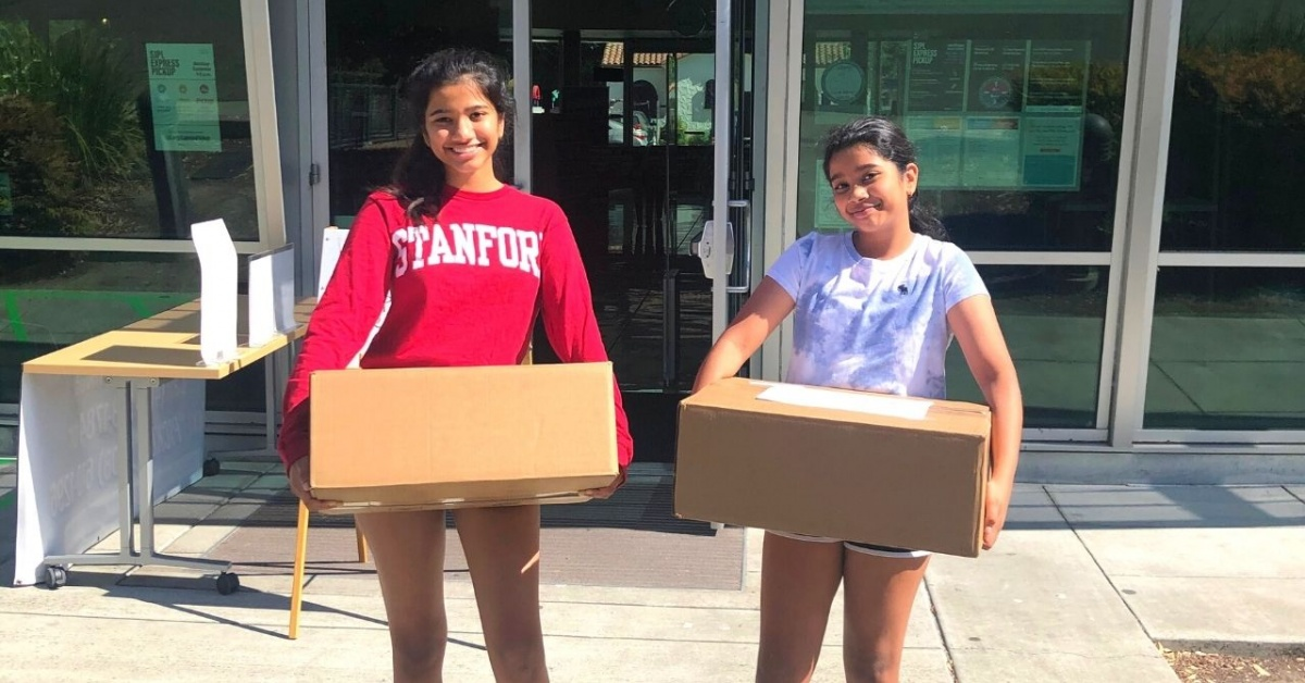 Two girls holding boxes in front of the library.
