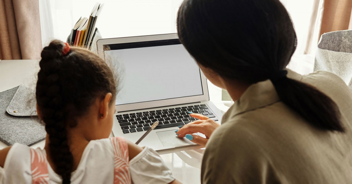 Mother helping daughter with homework on a laptop.