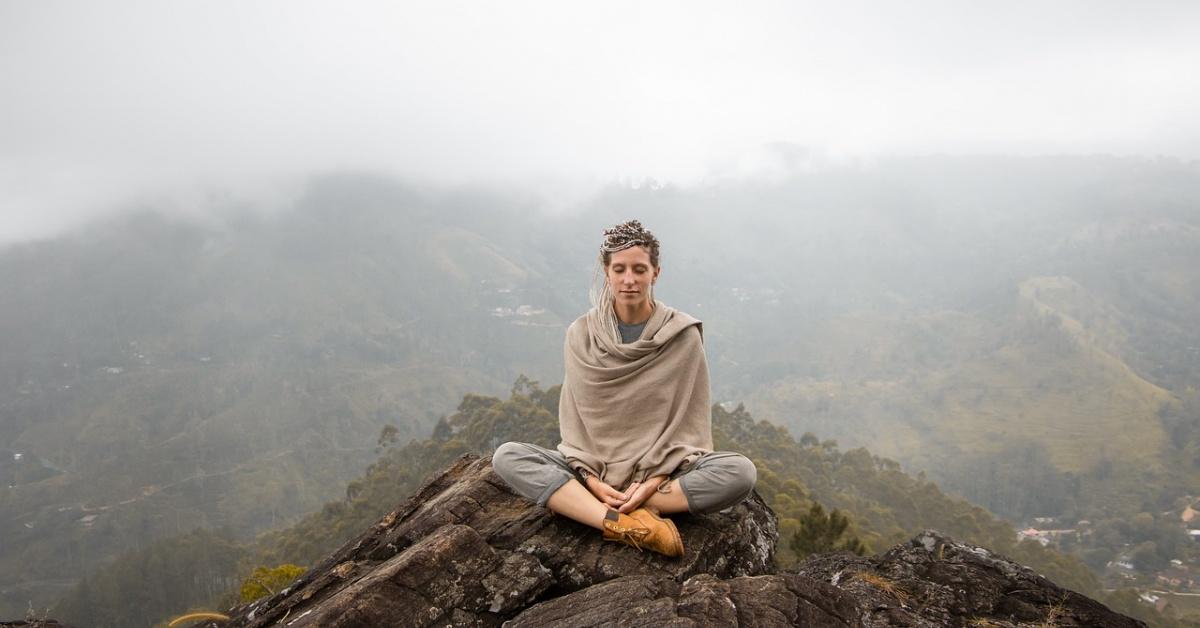 Señora sentada con las piernas cruzadas en la cima de una montaña