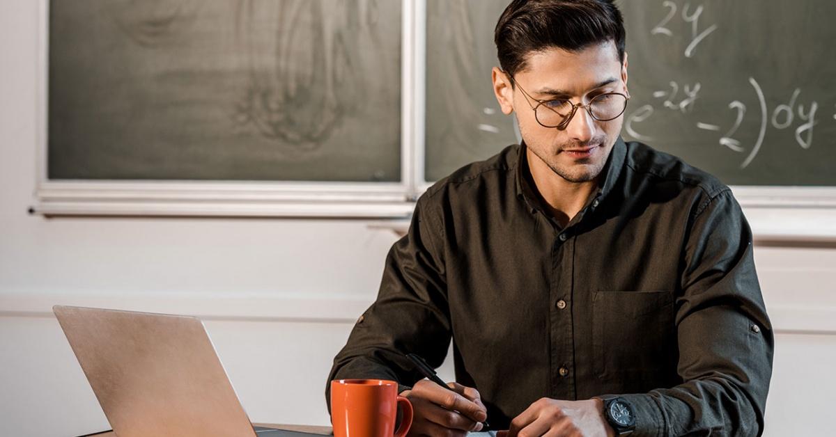 Giáo viên trên bàn với máy tính xách tay nghiên cứu giáo án của mình.