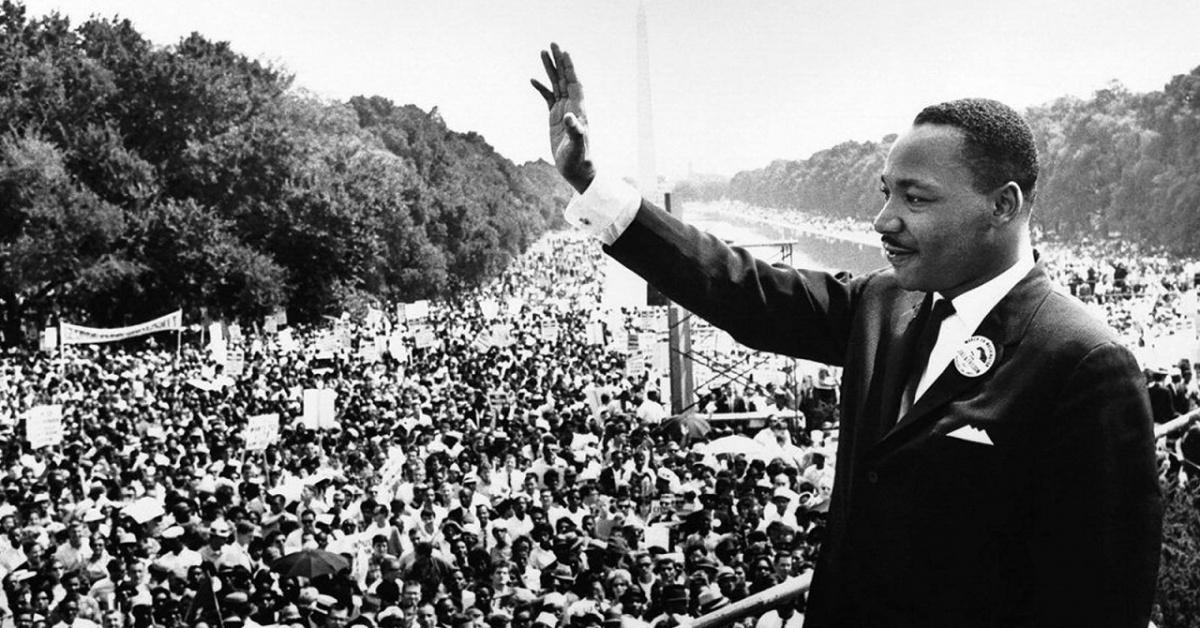 Martin Luther King Jr levanta la mano hacia una gran multitud en el Capitolio estatal.