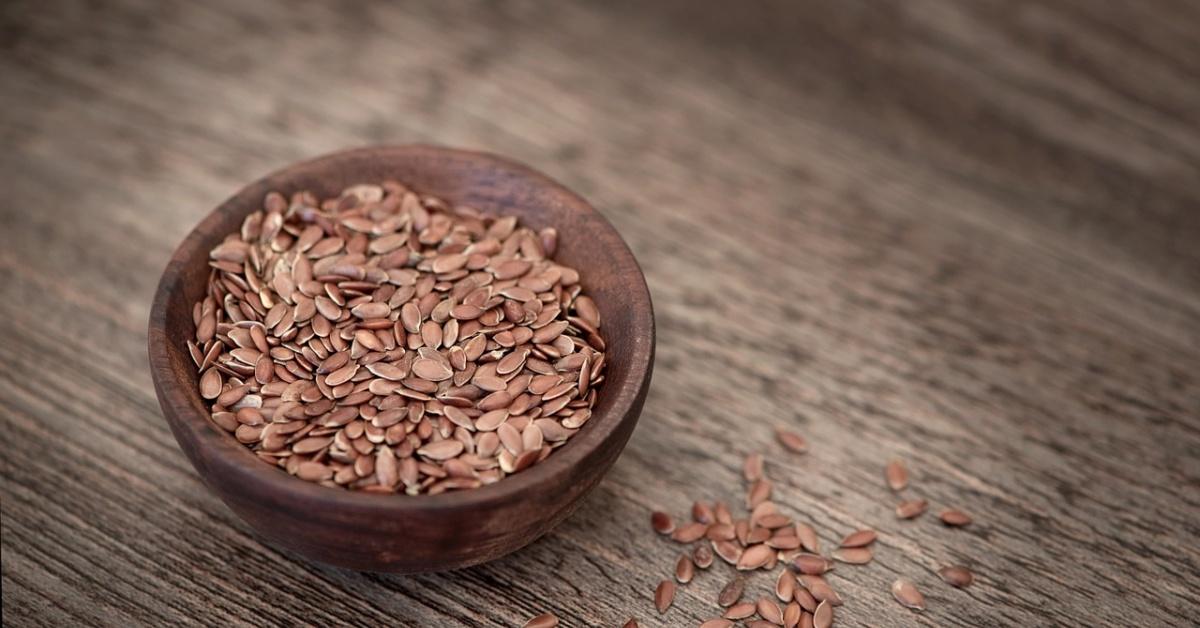 Un cuenco de madera lleno de semillas de lino sobre una mesa de madera.