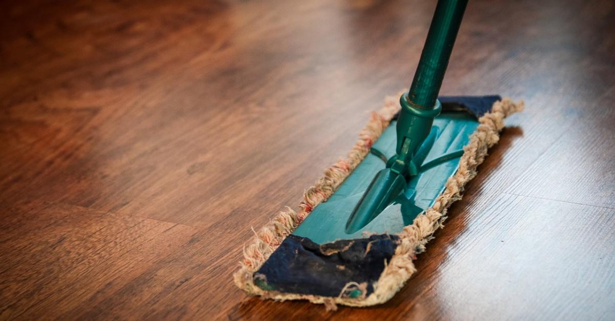 Swiffer verde con una almohadilla reutilizable limpia un piso de madera.