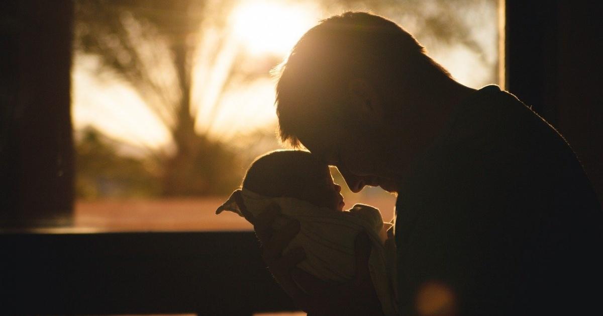 El hombre acuna al bebé y apoya la frente contra la frente del bebé con la puesta de sol de fondo.