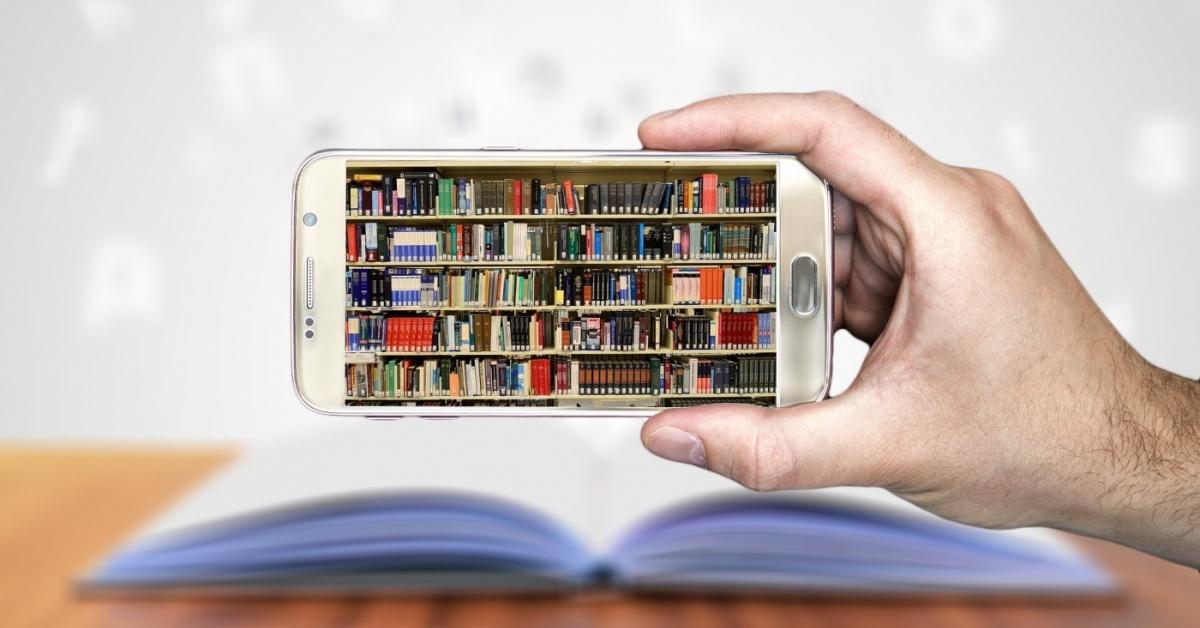 Imagen de la mano de una persona sosteniendo un teléfono inteligente que tiene imágenes de libros en los estantes.