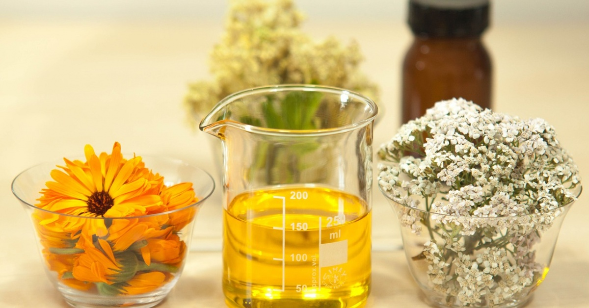 Vaso de precipitados lleno de líquido amarillo entre dos intestinos de vidrio con flores.