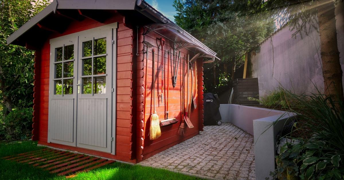Cobertizo de jardín rojo con puertas dobles blancas sobre césped de hierba verde.