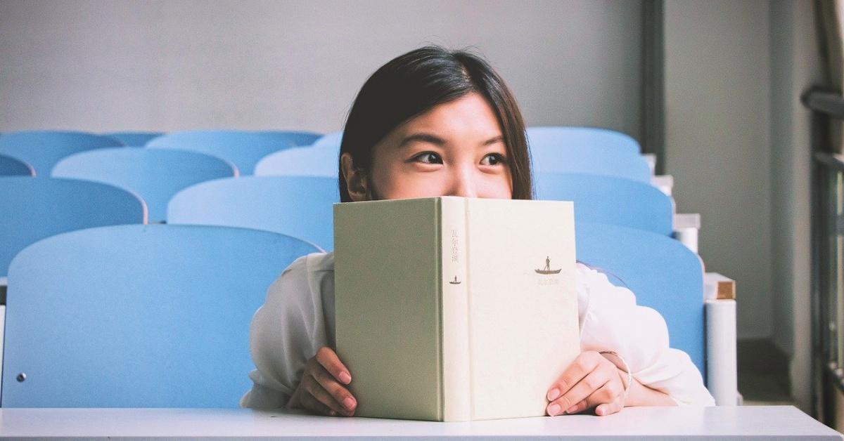 Mujer mirando por encima de un libro abierto en un aula.