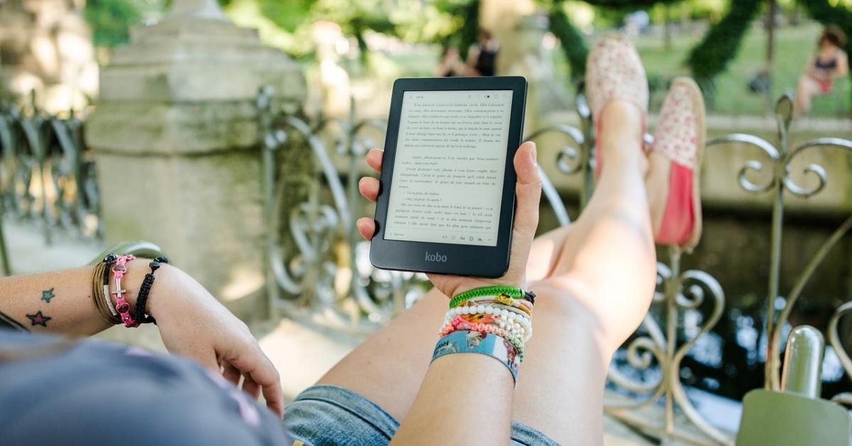 Imagen de una persona que lee un texto en un eReader con los pies apoyados