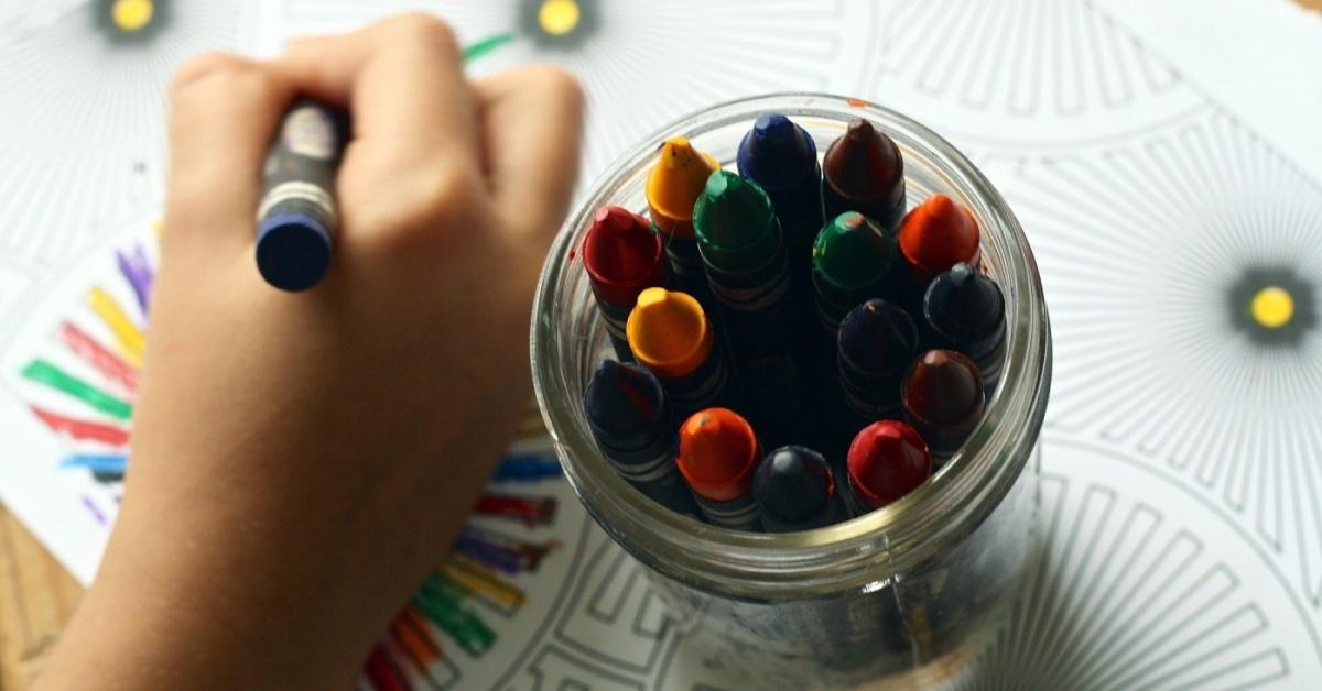 La mano de un niño sostiene un crayón haciendo un dibujo. Junto al niño hay un pequeño frasco de vidrio lleno de crayones de diferentes colores.