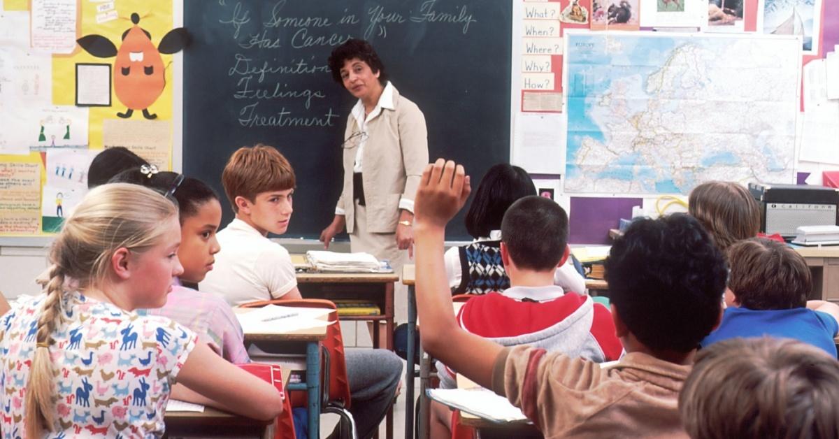 Jóvenes estudiantes y un profesor en un aula.