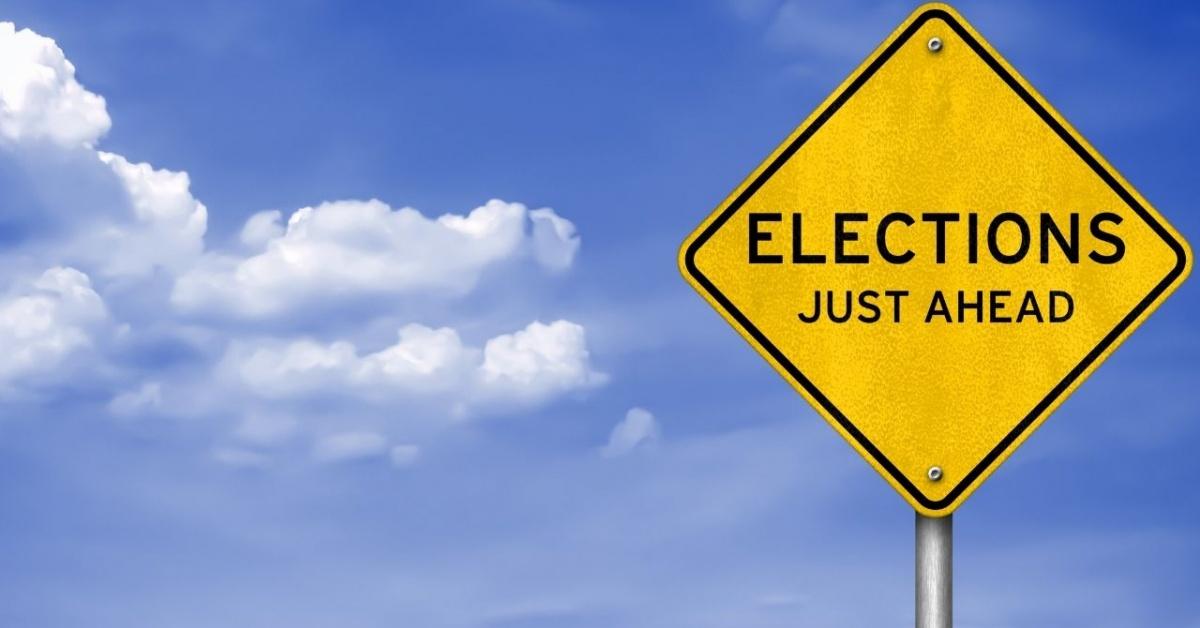 Cielo abierto con letrero en forma de diamante en primer plano que dice elecciones justo por delante