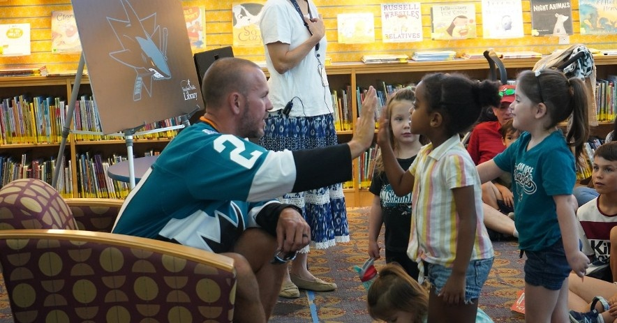 Children high-five a San Jose Sharks hockey player at a special story hour honoring the SJ Sharks library card.