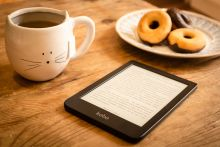 A Kindle is on top of a wooden table, surrounded by a cat-shaped mug filled with tea and a plate with donuts.