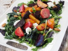Large serving platter with root vegetables, peaches, and tomatoes placed on a bed of mixed greens.