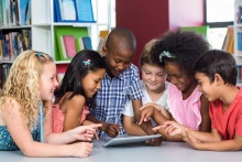 Six young children are grouped around a tablet device at a table in a library.