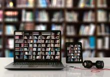 Una computadora portátil abierta y un teléfono inteligente en una mesa muestran una gran pantalla de libros en sus pantallas. Un iPod y auriculares también están sobre la mesa, y una gran estantería está en el fondo.