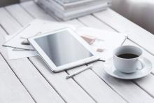 Một thiết bị máy tính bảng nằm trên một số tạp chí trên bàn với một tách cà phê bên cạnh.