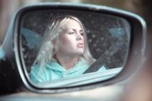 Jovencita en el espejo lateral del coche