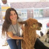 Staff member Smiling and petting a llama