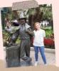 Escritor, TracYo, de pie junto a una estatua de Walt Disney y Mickey Mouse.